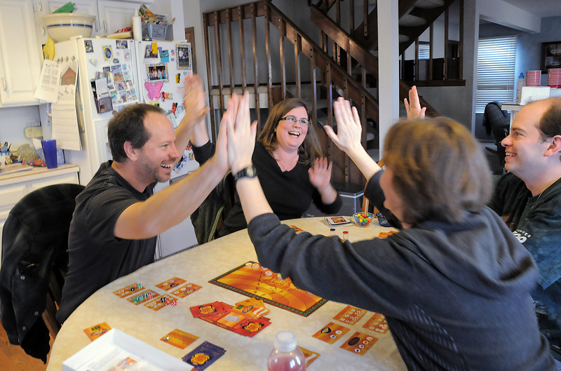 BE0127game03<br /> John Morris, left, and his wife Shawna give a high five to Lisa Bjornseth and Brian Modreski after they won the cooperative food preparation game, Wok Star, at the 104th gaming event by Time Well Spent Games at Dave Jones home in Eagle Trace on Saturday. <br /> <br /> January 22, 2011<br /> staff photo/David R. Jennings