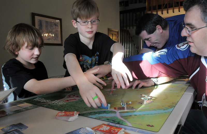 "BE0127game01<br /> Blake Manoff, 9, left, Jordan Grow, 9, John Rollins and Dave Jones move game pieces while playing ""Wings of War"" game at the 104th gaming event by Time Well Spent Games at Dave Jones home in Eagle Trace on Saturday. <br /> <br /> January 22, 2011<br /> staff photo/David R. Jennings"