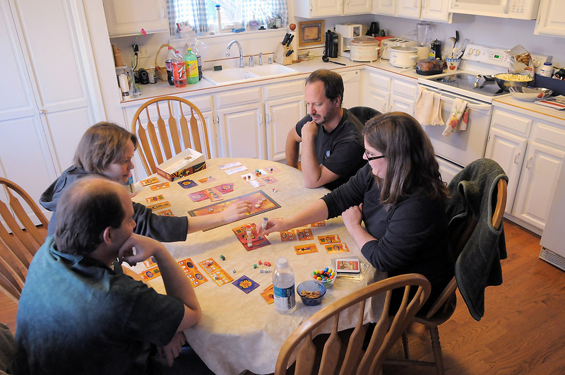 BE0127game02<br /> Brian Modreski, left, Lisa Bjornseth play Wok Star a food related game with John and Shawna Morris in the kitchen of  Dave Jones home in Eagle Trace at the 104th gaming event by Time Well Spent Games on Saturday. <br /> <br /> January 22, 2011<br /> staff photo/David R. Jennings