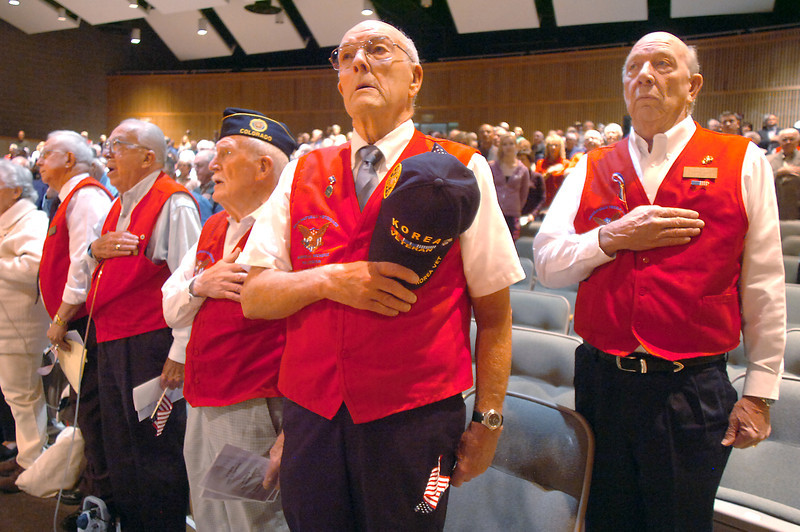 Broomfield Veteran's Memorial Museum members Bob Seeber, left, Bob Davenport, Wayne Burt, Jim Sparks and Larry Hasty place their hands over their hearts during the singing of the National Anthem during the annual Veterans Day ceremony at Broomfield High School on Friday.<br /> <br /> <br /> November 11, 2011<br /> staff photo/ David R. Jennings