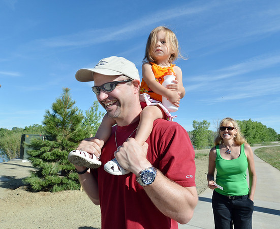 Steve Otto carries his grand daughter Ava Dooley, 2, on his shoulders as they walk the trail around Alexx and Michael's Pond during the 11th Annual Trail Adventure in the Westlake neighborhood on Saturday. Steve Otto is the father of Michael Otto for whom the pond was co-named.<br /> June 2, 2012 <br /> staff photo/ David R. Jennings