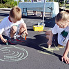 Will Tennyson, 7, left, and his sister Tanna, 11, make chalk drawings in the parking lot of the LDS Church during the 11th Annual Trail Adventure in the Westlake neighborhood on Saturday.<br /> June 2, 2012 <br /> staff photo/ David R. Jennings