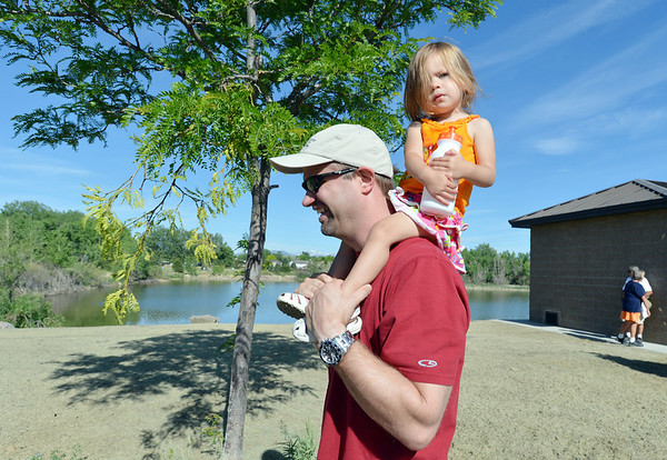 Steve Otto carries his grand daughter Ava Dooley, 2, on his shoulders as they walk the trail around Alex and Michael's Pond during the 11th Annual Trail Adventure in the Westlake neighborhood on Saturday. Steve Otto is the father of Michael Otto for whom the pond was co-named.<br /> June 2, 2012 <br /> staff photo/ David R. Jennings