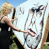 Charlotte Rose, 16, adds to the 'artwall' at Broomstock on Thursday.<br /> Photo: David Jennings