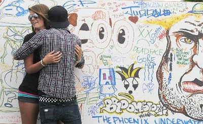 Taylor Castaneda, 16, and Travis Jenks, 16, hug in front of the 'artwall' at Broomstock on Thursday. Photo: David Jennings