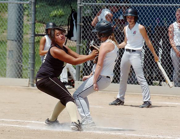Colorado Stars first baseman Vic Macias, left, tags out Kansas City Glroy's Paige Hayden during the 2011 Colorado Fireworks Softball Tournament 12U softball championship game at Community Park on Monday.<br /> <br /> July 4, 2011<br /> staff photo/ David R. Jennings
