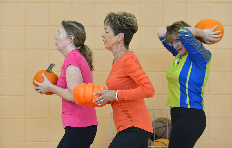 Janet Irwin, left, Judi Redington and Bette Erickson carry their pumpkins while running in the gym during the Great Pumpkin Workout at the Paul Derda Recreation Center on Thursday.<br /> October 25, 2012<br /> staff photo/ David R. Jennings
