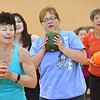 Jean Rosecrans, center, uses her green pumpkin for a weight during an exercise at the Great Pumpkin Workout at the Paul Derda Recreation Center on Thursday.<br /> October 25, 2012<br /> staff photo/ David R. Jennings