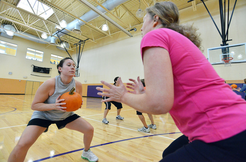 Theresa Irwin, left, prepares to hand a pumpkin to her mother Janet Irwin while exercising during the Great Pumpkin Workout at the Paul Derda Recreation Center on Thursday.<br /> October 25, 2012<br /> staff photo/ David R. Jennings
