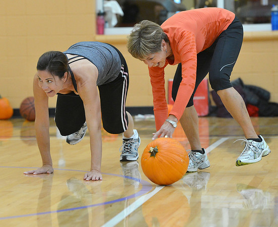 Judi Redington, right, rolls a pumpkin with her daughter Shari Graham during the Great Pumpkin Workout at the Paul Derda Recreation Center on Thursday.<br /> October 25, 2012<br /> staff photo/ David R. Jennings
