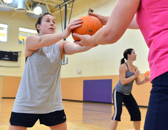 Theresa Irwin, left, hands off a pumpkin to her mother Janet Irwin while exercising during the Great Pumpkin Workout at the Paul Derda Recreation Center on Thursday.<br /> October 25, 2012<br /> staff photo/ David R. Jennings