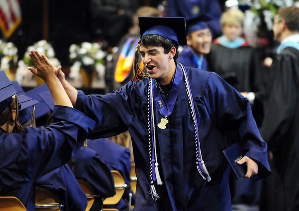 Schyler Vargus gives a high five to a fellow graduate after receiving his diploma during Legacy High School's graduation ceremony at Coors Event Center at the University of Colorado on Monday.<br /> <br /> May 14, 2012 <br /> staff photo/ David R. Jennings