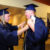 Jordyn Johnson, left, helps Ty Overboe with his academic cords before  Legacy High School's graduation ceremony at Coors Event Center at the University of Colorado on Monday.<br /> <br /> May 14, 2012 <br /> staff photo/ David R. Jennings