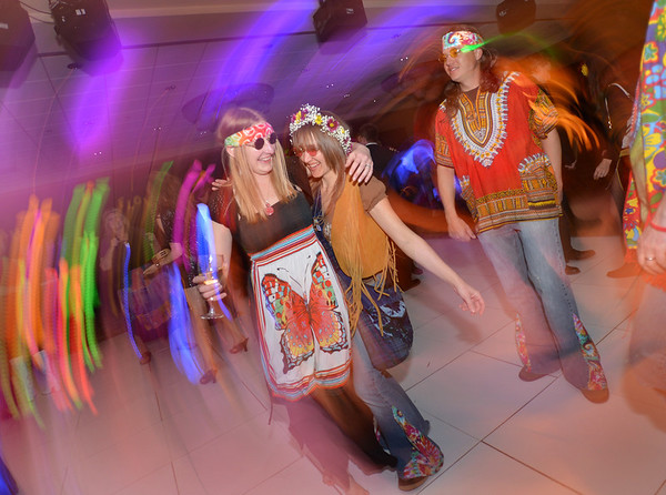 """Bal Swan teachers Janet Gonzalez, left, and Sara Pringle dance with Pringle's husband, Chad, dance during the 48th annual Bal Swan Ball with the 1960's theme of """"Peace, Love and Bal Swan"""" at the Omni Interlocken Hotel Resort on Saturday.<br /> March 2, 2013<br /> staff photo/ David R. Jennings"""
