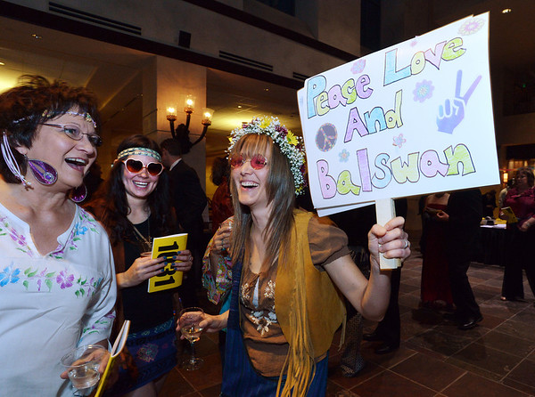 "Bal Swan teacher Sara Pringle, right, holds up a ""protest"" sign with her mother Joy Anderson, left, and Lacey Guerin during the 48th annual Bal Swan Ball with the 1960's theme of ""Peace, Love and Bal Swan"" at the Omni Interlocken Hotel Resort on Saturday.<br /> March 2, 2013<br /> staff photo/ David R. Jennings"