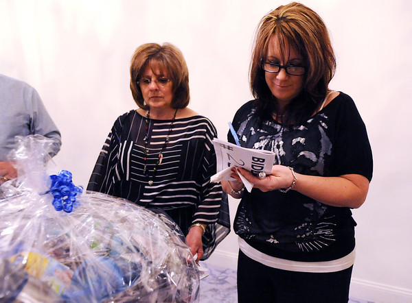 Lina Fedysyshyn, left, and Cyndy Benschop take notes while figuring out which baskets to bid on for the silent auction during the 3rd annual Eagle Sports Gala for Broomfield High School Athletics at the Church Ranch Event Center on Friday.<br /> March 16,  2012 <br /> staff photo/ David R. Jennings