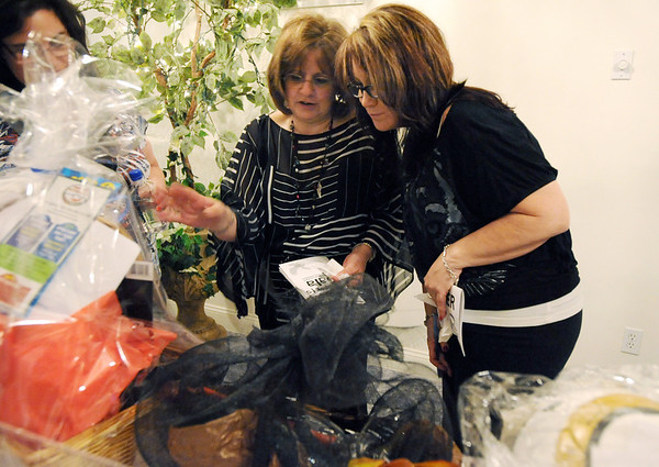 Lina Fedysyshyn, left, and Cyndy Benschop look at baskets to bid on for the silent auction during the 3rd annual Eagle Sports Gala for Broomfield High School Athletics at the Church Ranch Event Center on Friday.<br /> March 16,  2012 <br /> staff photo/ David R. Jennings