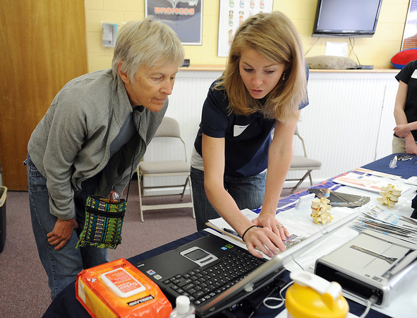 Lindsey Green with Fox Choropractic, right, explains results of a foot exam to Peggy Baxter  during the 9Health Fair at Broomfield United Methodist Church on Saturday.<br /> <br /> April 21, 2012 <br /> staff photo/ David R. Jennings