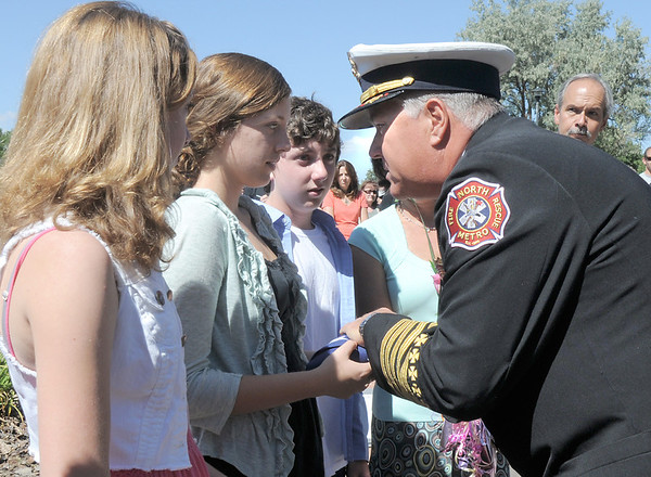 North Metro Fire Rescue Chief Joe Bruce presents a U.S. flag to the Siena Faughnan, 17, and her siblings Juliet, 14, left, and Liam, 12, in honor of their father Chris Faughnan who died in the Wrodl Trade Center attacks on Set. 11, 2001, during the 9/11 Commemorative Ceremony at the 9/11 Memorial in Community Park on Sunday.<br /> September 11, 2011<br /> staff photo/ David R. Jennings