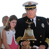 North Metro Fire Rescue Chief Joe Bruce rings the fire bell three times honor the fallen of the Sept. 11, 2001 attacks with the family of Chris Faughnan, who died in the attacks, during the 9/11 Commemorative Ceremony at Community Park on Sunday.<br /> September 11, 2011<br /> staff photo/ David R. Jennings