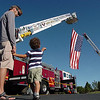Clay Romine with his son Cooper, 3, look at the large U.S. flag hanging between two North Metro Fire district tower trucks before the 9/11 Commemorative Ceremony at the 9/11 Memorial in Community Park on Sunday.<br /> September 11, 2011<br /> staff photo/ David R. Jennings