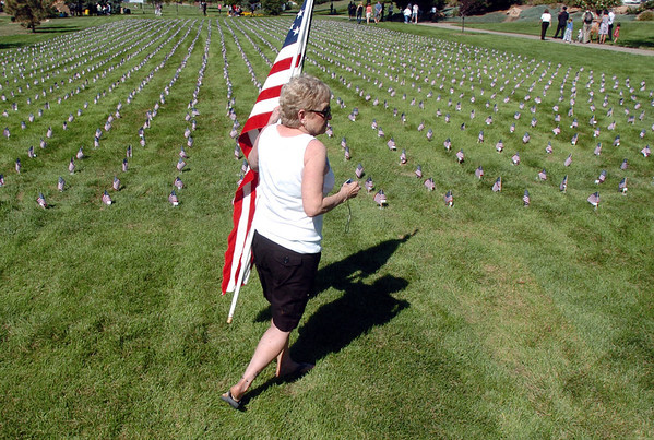 Lynn Riley looks for a flag of New York firefighter Rubin Correra in the mini-healing field before the 9/11 Commemorative Ceremony at the 9/11 Memorial in Community Park on Sunday. Riley finally did find the flag.<br /> September 11, 2011<br /> staff photo/ David R. Jennings