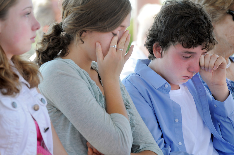 Juilet Faughnan, 14, left, Siena, 17, and Liam, 12, cry as their  father Chris Faughnan, who died in the World Trade Center attacks on Sept. 11, 2001, is remembered during the 9/11 Commemorative Ceremony at the 9/11 Memorial in Community Park on Sunday.<br /> September 11, 2011<br /> staff photo/ David R. Jennings