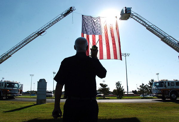 Battalion Chief Bruce Gunter talks on the radio to fire fighters hanging the large U.S. flag between two fire tower trucks before the 9/11 Commemorative Ceremony at the 9/11 Memorial in Community Park on Sunday.<br /> September 11, 2011<br /> staff photo/ David R. Jennings
