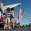 Clay Romine with his sons Cooper, 3, and Jaxon, 5, look at the large U.S. flag hanging between two North Metro Fire district tower trucks before the 9/11 Commemorative Ceremony at the 9/11 Memorial in Community Park on Sunday.<br /> September 11. 2011<br /> staff photo/ David R. Jennings