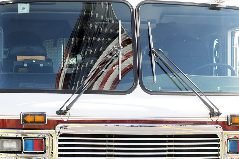 The large U.S. flag is reflected in the windshield of a North Metro Fire Rescue tower truck during the 9/11 Commemorative Ceremony at the 9/11 Memorial in Community Park on Sunday.<br /> September 11, 2011<br /> staff photo/ David R. Jennings