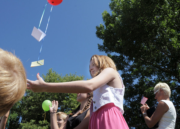 "Juliet Faughnan, 14, releases a ballon wiht the simple message to her late father Chris, "" I love you"" , after the 9/11 Commemorative Ceremony at the 9/11 Memorial in Community Park on Sunday.<br /> September 11, 2011<br /> staff photo/ David R. Jennings"