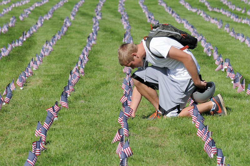 Kollin Skattum, 15, looks at flags in the mini-healing field before the 9/11 Commemorative Ceremony at the 9/11 Memorial in Community Park on Sunday.  Skattum came to the mini-healing field to kkeo the memory of the people killed in the Sept. 11 2001 attacks.<br /> September 11, 2011<br /> staff photo/ David R. Jennings