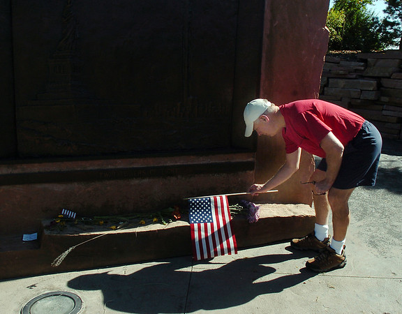 Nick Marble places a flag at the base of the New York  part of the the 9/11 Memorial before the 9/11 Commemorative Ceremony at Community Park on Sunday. Marble said he wanted to honor the courage of the people on Flight 93.<br /> September 11, 2011<br /> staff photo/ David R. Jennings