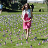 Juliet Faughnan, 14, carries a flag from the mini-healing field after the 9/11 Commemorative Ceremony in Community Park on Sunday.<br /> September 11, 2011<br /> staff photo/ David R. Jennings