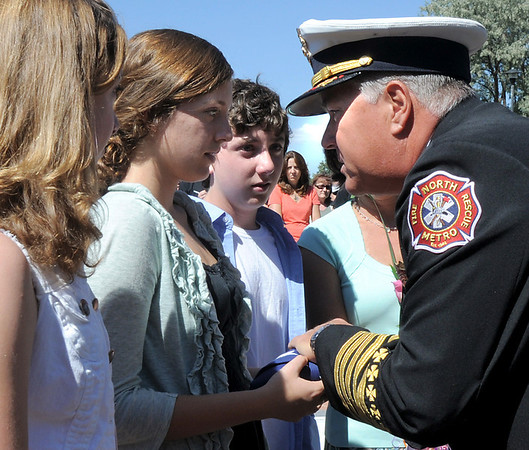 North Metro Fire Rescue Chief Joe Bruce presents a U.S. flag to the Siena Faughnan, 17, and her siblings Juliet, 14, left, and Liam, 12, in honor of their father Chris Faughnan who died in the World Trade Center attacks on Set. 11, 2001, during the 9/11 Commemorative Ceremony at the 9/11 Memorial in Community Park on Sunday.<br /> September 11, 2011<br /> staff photo/ David R. Jennings