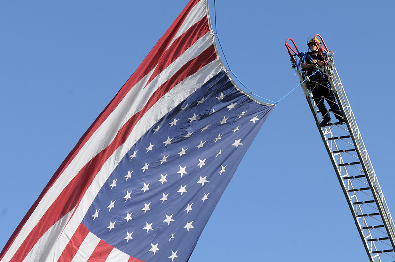 North Metro Fire Rescue firefighter Doug Finley  helps hang a large U.S. flag between two ladder trucks before the 9/11 Commemorative Ceremony at the 9/11 Memorial in Community Park on Sunday.<br /> September 11, 2011<br /> staff photo/ David R. Jennings