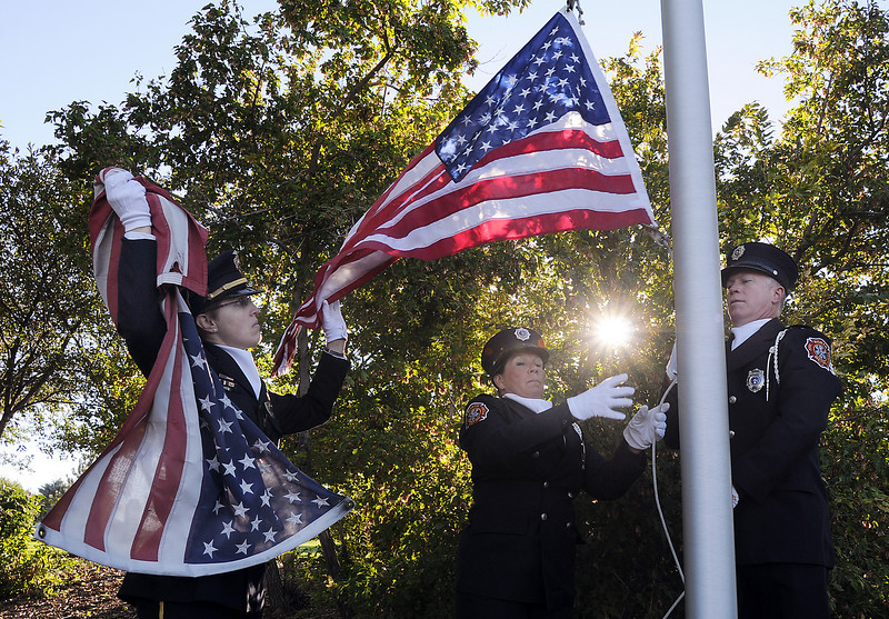 BE0919NINE06<br /> Broomfield officer Carol Lucero, left, and North Metro Fire firefighter  Audrey Neary and Lt. Curtis Krantz change the flag at the 9/11 Memorial during the ceremony on Saturday.<br /> <br /> September 11, 2010<br /> staff photo/David R. Jennings