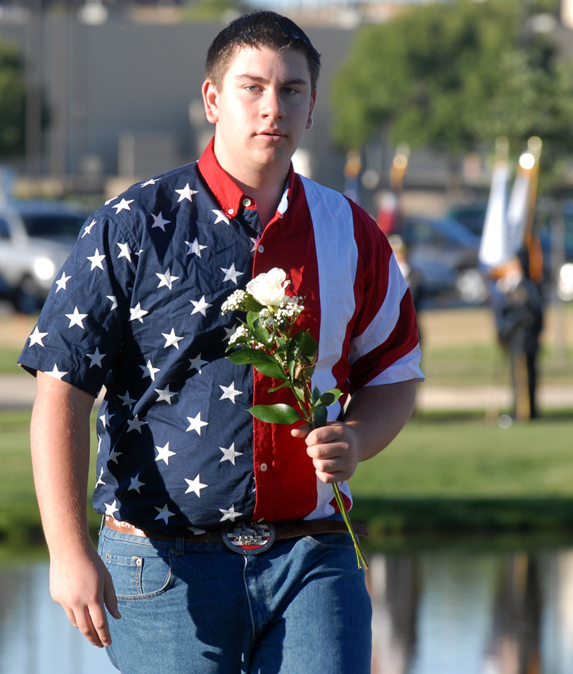 BE0919NINE13<br /> Justin Shrader, 15, brings flowers to place on the sculptures of the 9/11 Memorial before the ceremony on Saturday.<br /> <br /> September 11, 2010<br /> staff photo/David R. Jennings