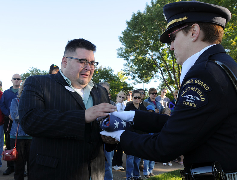 BE0919NINE03<br /> Joshua Miller accepts a flag in memory of Deora Bodley, who died on Flight 93, from Broomfield officer Carol Lucero during the ceremony at the 9/11 Memorial on Saturday.<br /> <br /> September 11, 2010<br /> staff photo/David R. Jennings