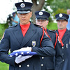 North Metro Fire Rescue District paramedic Ken Work carries the flag of the 9/11 Memorial to be given to the Faughnan family  during the 9/11 Memorial ceremony at the 9/11 Memorial at Community Park on Tuesday.<br /> September 11, 2012<br /> staff photo/ David R. Jennings