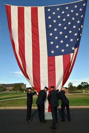 North Metro Fire Rescue District Honor Guard members take the large flag down after the 9/11 ceremony at the 9/11 Memorial at Community Park on Tuesday.<br /> September 11, 2012<br /> staff photo/ David R. Jennings
