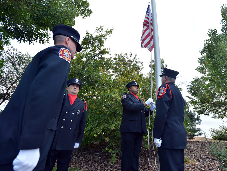 The North Metro Fire Rescue Honor Guard brings down the flag of the 9/11 Memorial during the ceremony at the 9/11 Memorial at Community Park on Tuesday.<br /> September 11, 2012<br /> staff photo/ David R. Jennings