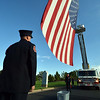 Members of the North Metro Fire Rescue District prepare to take the large flag hanging between two ladder trucks down after  the 9/11 ceremony at the 9/11 Memorial in Community Park on Tuesday.<br /> September 11, 2012<br /> staff photo/ David R. Jennings