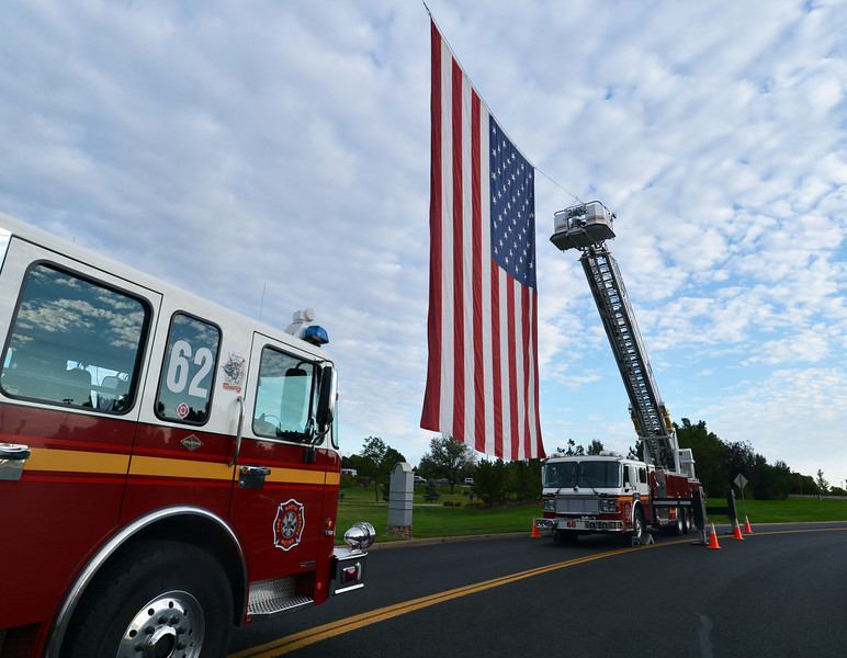 North Metro Fire Rescue District firefighters posted a large flag flown between two ladder trucks for the 9/11 ceremony at the 9/11 Memorial at Community Park on Tuesday.<br /> September 11, 2012<br /> staff photo/ David R. Jennings