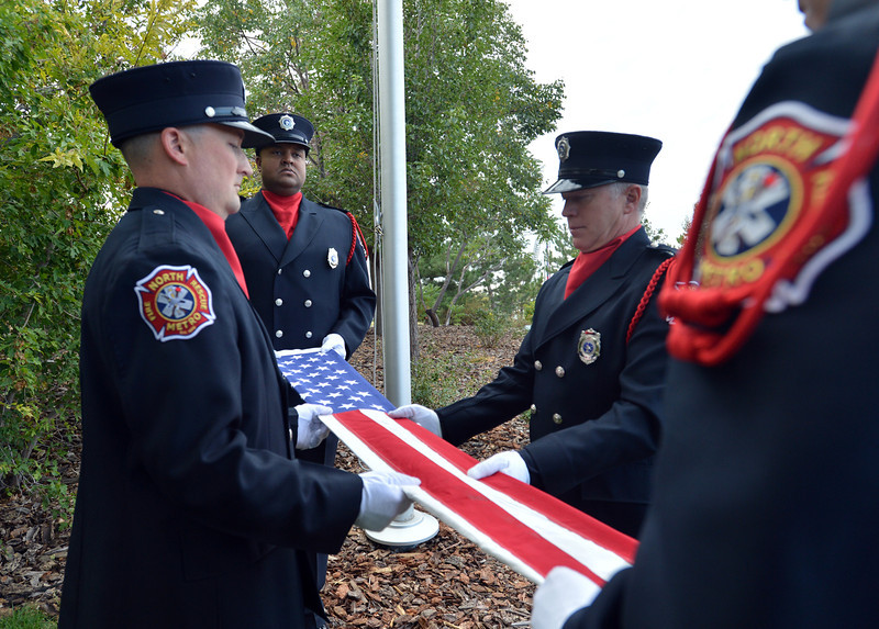 The North Metro Fire Rescue Honor Guard folds the flag of the 9/11 Memorial during the ceremony at the 9/11 Memorial at Community Park on Tuesday.<br /> September 11, 2012<br /> staff photo/ David R. Jennings