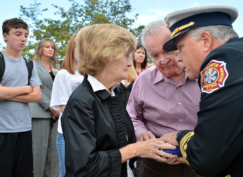 North Metro Fire Chief Joe Bruce, right, gives the flag to Joan and Tom Faughnan  in honor of their son Chris Faughnan who died in the 9/11 attacks during the 9/11 ceremony at the 9/11 Memorial  in Community Park on Tuesday.  LIam Faughnan, 13, left, is Chris Faughnan's son.<br /> September 11, 2012<br /> staff photo/ David R. Jennings