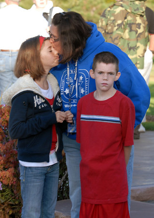 "Sonya Acker, center, kisses her daughter Samantha, 11, with her son Austyn, 9, after singing ""America the Beautiful"" to themselves at the 9/11 Memorial in Community Park in Broomfield on Friday morning.<br /> <br /> Sept. 11, 2009<br /> Staff photo/David R. Jennings"