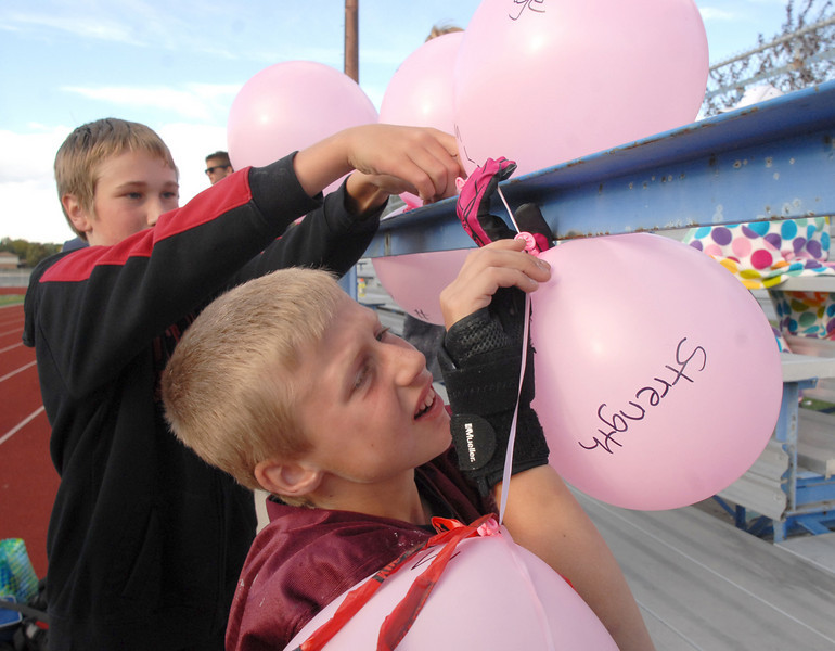 Joshua Cox, 11, right, and Cal Lively, 13, help decorate the east stands with pink balloons for the Broomfield Youth Football Buckeyes team who dedicated their playoff game to Michelle Lucero, a breast cancer patient, on Saturday at Elizabeth Kennedy Stadium.<br /> October 9, 2010<br /> staff photo/David R. Jennings