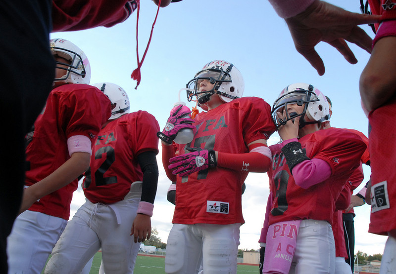 Ryan Mazzola, #17, center, with the Broomfield Youth Football team the Buckeyes lead the dedication of their Saturday playoff game to team parent Michelle Lucero, a breast cancer patient, at Elizabeth Kennedy Stadium.<br /> October 9, 2010<br /> staff photo/David R. Jennings