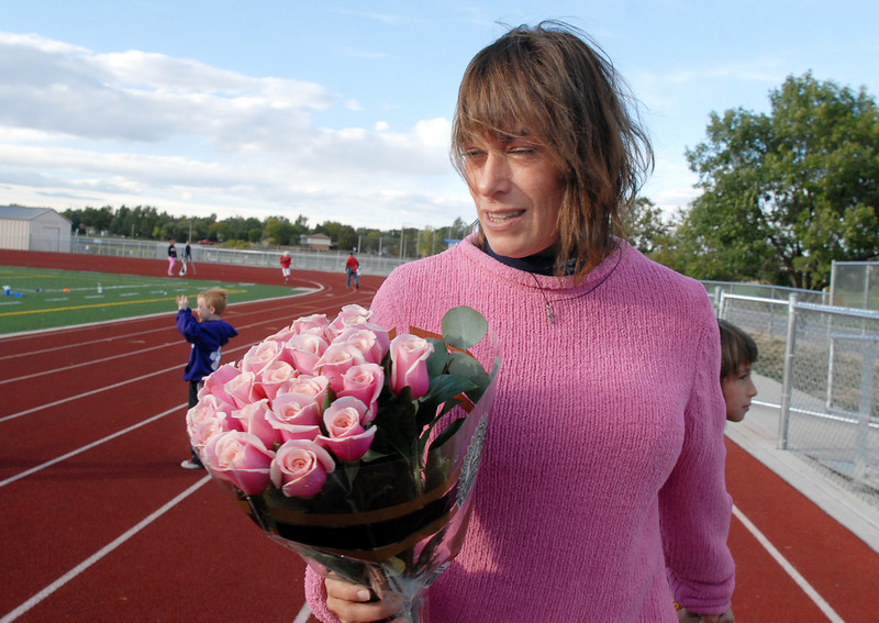 Michelle Lucero holds a bouquet of pink roses given to her by the Broomfield Youth Football team the Buckeyes who dedicated their playoff game to Lucero, a breast cancer patient, on Saturday at Elizabeth Kennedy Stadium.<br /> October 9, 2010<br /> staff photo/David R. Jennings